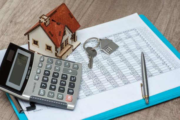 Relevé de compte, calculatrice, stylo et porte-clefs en forme de maison sur un bureau