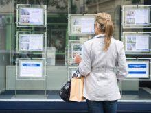 Femme qui regarde la vitrine d'une agence immobilière